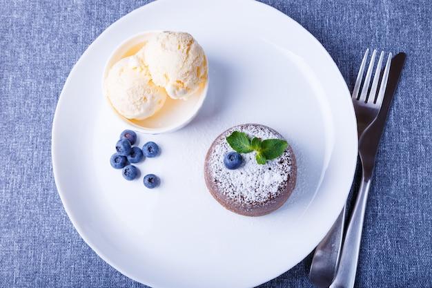 Gâteau fondant au chocolat lava cake avec glace vanille myrtilles et menthe gros plan