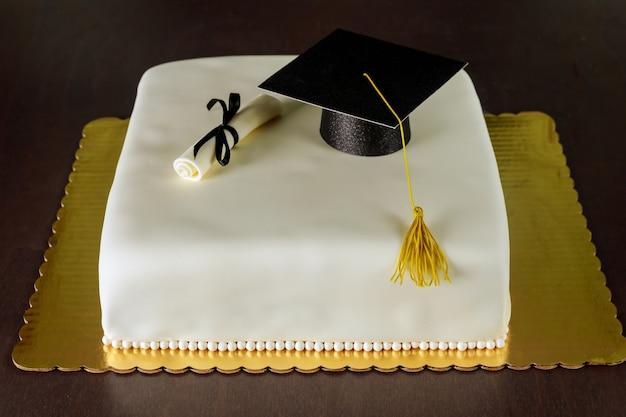 Gâteau fondant de remise des diplômes avec chapeau et décoration de diplôme pour la fête.
