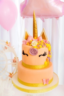 Gâteau en forme de licorne avec une grande corne dorée