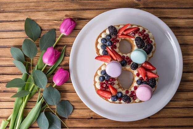 Gâteau en forme de numéro 8 décoré de baies et de fleurs de tulipes