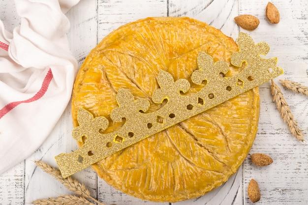 Gâteau galette des rois fait maison avec couronne de roi à la main. gâteau epiphanie français traditionnel avec amande moulue