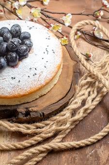Un gâteau un gâteau appétissant avec des raisins noirs à côté des branches d'arbres