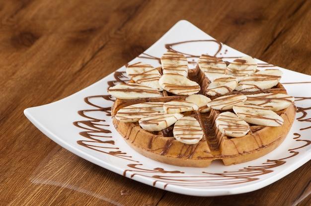 Gâteau gaufrette dans une assiette carrée blanche sur une surface en bois laqué avec reflet