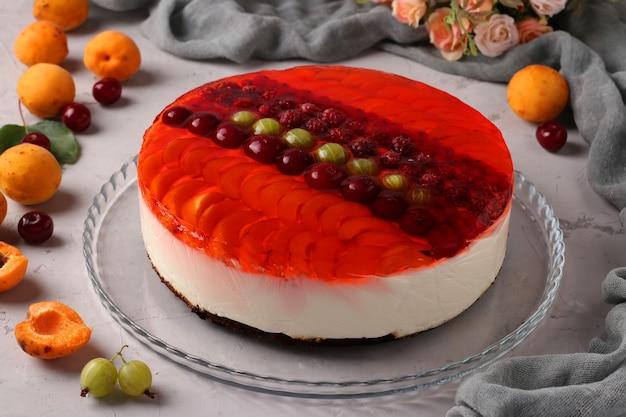 Gâteau à la gelée rouge avec des baies et de la crème sure sur gris