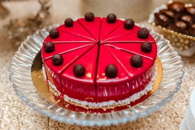 Gâteau glacé rouge sur la table, coupé en morceaux. décoré de boules de chocolat. barre de chocolat