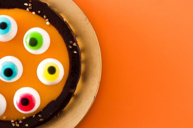 Gâteau d'halloween avec une décoration yeux bonbon sur orange.