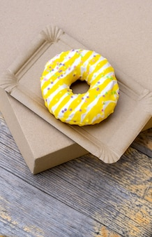 Gâteau jaune sur la plaque de livraison de papier sur le fond en bois, vue de dessus.
