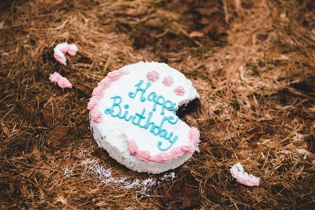 Gâteau de joyeux anniversaire sur des feuilles séchées brunes