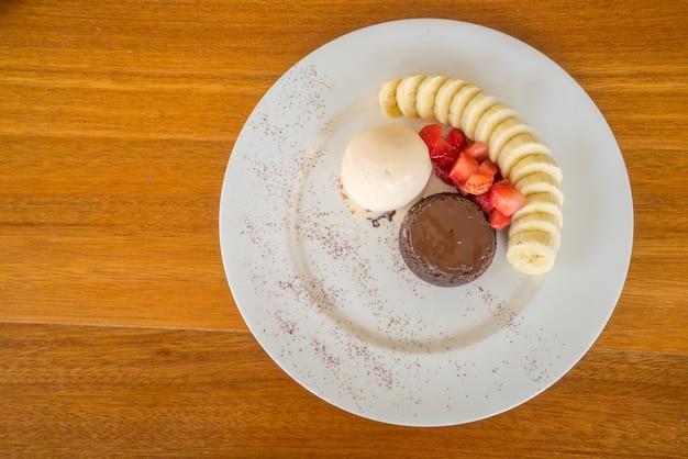 Gâteau de lave au chocolat avec glace à la vanille, garniture à la fraise et à la banane