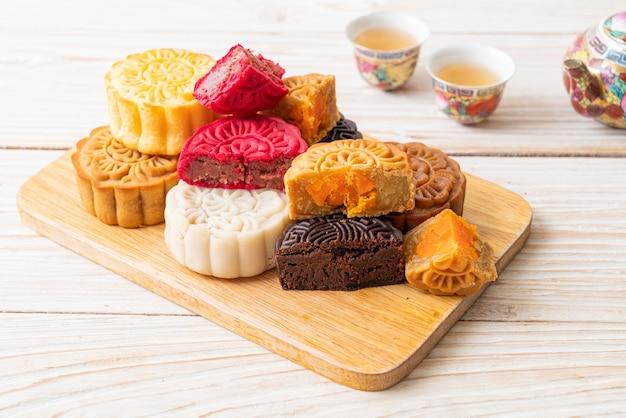 Gâteau de lune chinois coloré aux saveurs mélangées sur plaque de bois