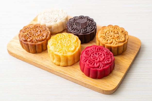 Gâteau de lune chinois coloré avec saveur mélangée sur plaque de bois