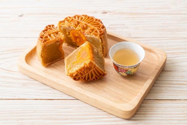 Gâteau de lune chinois durian et saveur de jaune d'oeuf avec du thé sur plaque de bois