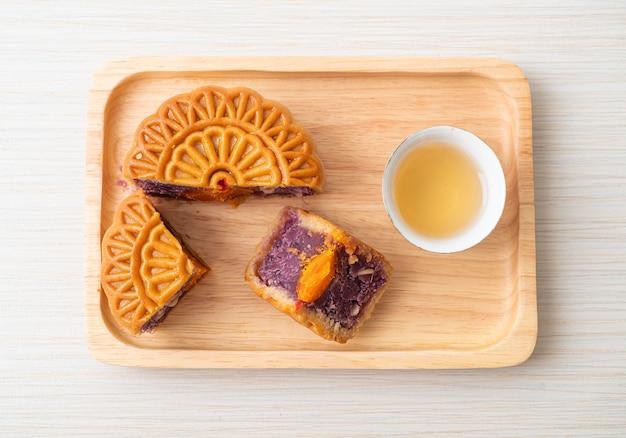 Gâteau de lune chinois saveur de patate douce violette avec du thé sur une plaque de bois