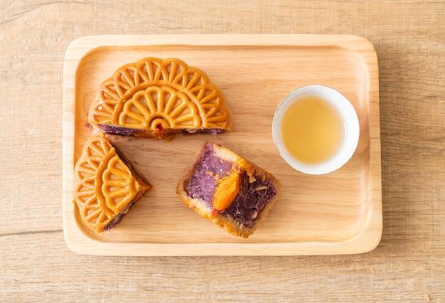 Gâteau de lune chinois saveur patate douce violette avec thé sur plaque de bois