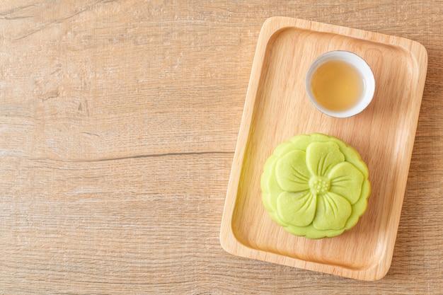 Gâteau de lune chinois saveur de thé vert avec du thé sur une plaque de bois