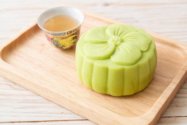Gâteau de lune chinois saveur de thé vert avec du thé sur plaque de bois