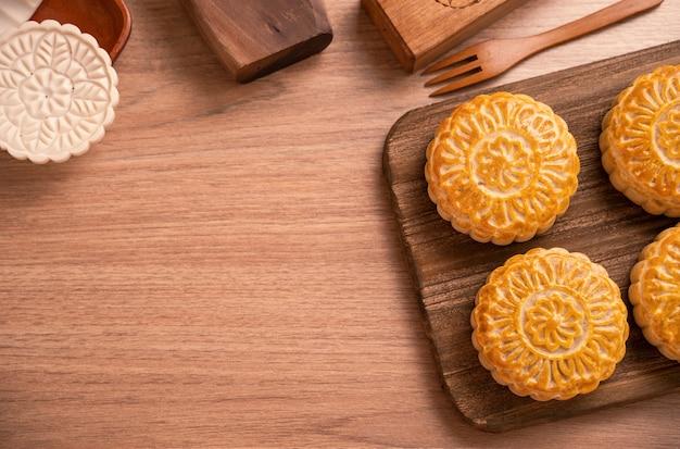Gâteau de lune de forme ronde mooncake - pâtisserie de style chinois pendant la fête de la mi-automne / fête de la lune sur fond et plateau en bois, vue de dessus, mise à plat
