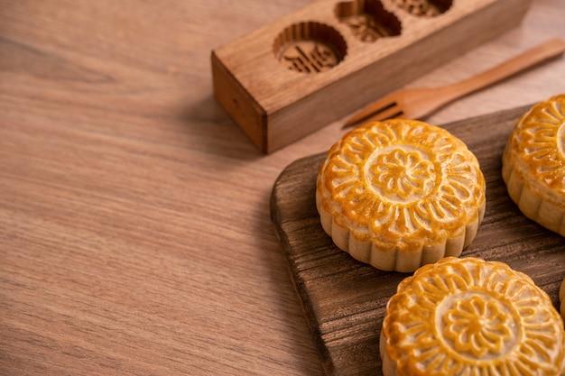 Gâteau de lune de forme ronde mooncake - pâtisserie traditionnelle de style chinois pendant la fête de la mi-automne / fête de la lune sur fond et plateau en bois, gros plan