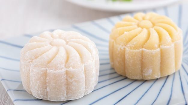 Gâteau de lune de peau de neige colorée, gâteau de lune neigeux sucré, dessert salé traditionnel pour le festival de la mi-automne sur fond en bois clair, gros plan, mode de vie.