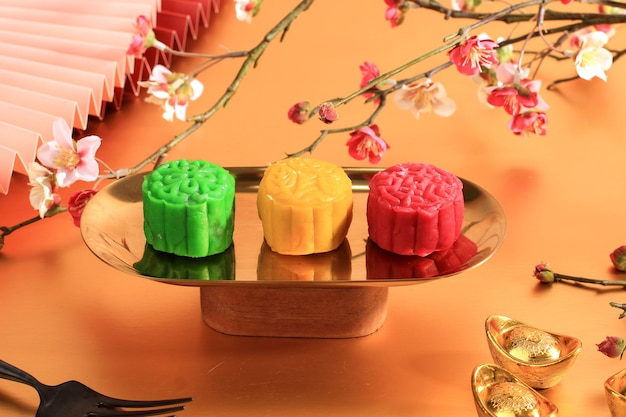 Gâteau de lune en peau de neige colorée. nouvelle variante de gâteau de lune, de crème pâtissière fourrée à la pâte de mochi, de pâte de haricots rouges ou de haricots mungo. moulé dans un moule mooncake.
