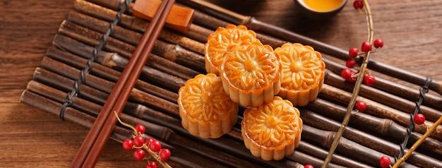 Gâteau de lune réglage de la table de gâteau de lune - pâtisserie traditionnelle chinoise de forme ronde avec des tasses à thé sur fond de bois, concept de la fête de la mi-automne, gros plan.
