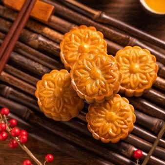 Gâteau de lune réglage de la table de gâteau de lune - pâtisserie traditionnelle chinoise avec des tasses à thé sur fond de bois, concept de festival de la mi-automne, vue de dessus, mise à plat.