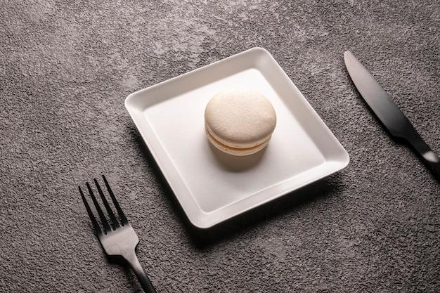Gâteau de macaron blanc dans une assiette blanche élégante. fermer. dessert pour le café, service de table, fourchette et couteau noirs