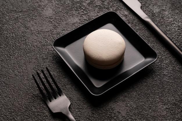 Gâteau macaron blanc dans une assiette carrée élégante photographie alimentaire minimaliste gros plan noir fourchette et cuillère