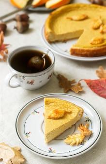 Gâteau maison américain traditionnel à la citrouille, décoré de biscuits sur un fond de citrouilles et de feuilles d'automne.
