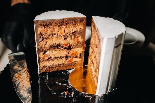 Gâteau de mariage au chocolat en tranches avec une garniture incroyable sur fond noir