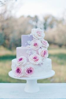 Gâteau de mariage aux couleurs pastel décoré de roses roses réalistes sur un arrière-plan flou du jardin, mise au point sélective