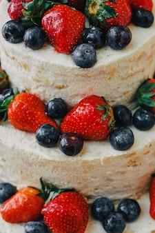 Gâteau de mariage blanc décoré de cerises, fraises et bleuets