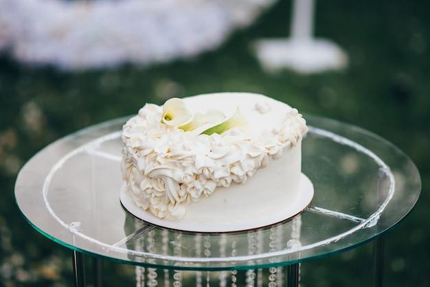 Gâteau de mariage blanc à un étage décoré de crème sous forme de fleurs se dresse sur une table en verre dans la nature