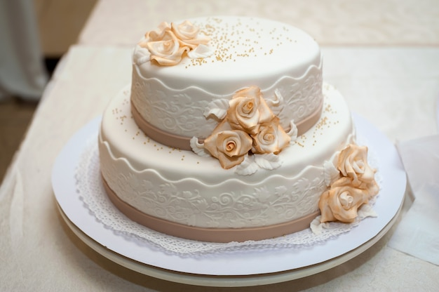 Gâteau de mariage blanc avec des fleurs. dessert pour les invités.