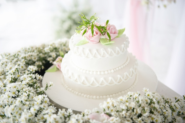 Gâteau de mariage blanc avec fleurs et plantes succulentes à la réception de l'avenue de mariage.