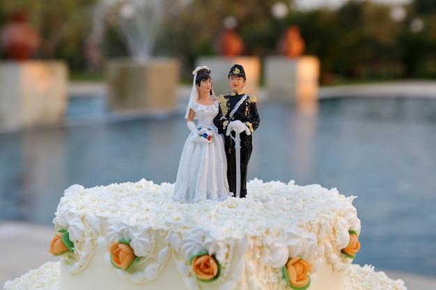 Gâteau de mariage avec la décoration de la mariée et du marié sur le dessus