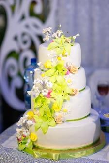 Gâteau de mariage décoré de fleurs de mastic sur un plateau