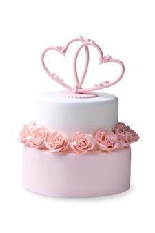 Gâteau de mariage décoré de fleurs roses et de coeurs isolés sur fond blanc