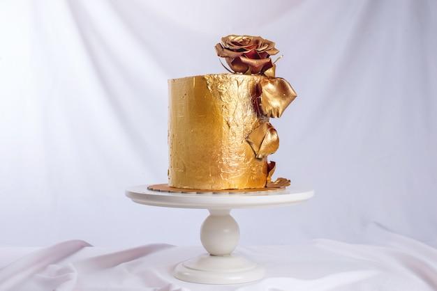 Gâteau de mariage décoré d'or, dégradé vert avec des fleurs dessinées à la main