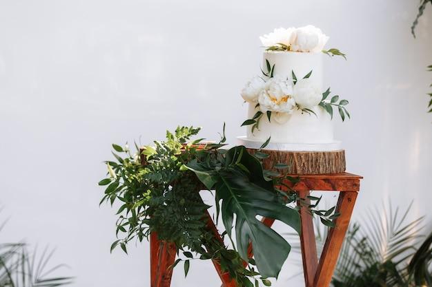 Gâteau de mariage élégant avec des fleurs et des plantes succulentes
