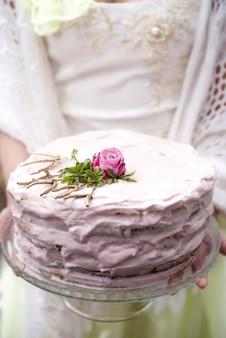 Gâteau de mariage entre les mains de la mariée se bouchent