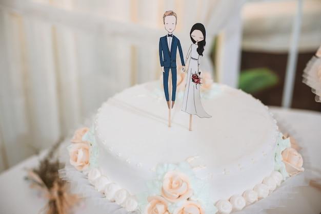 Gâteau de mariage avec des figurines drôles d'époux et épouse.