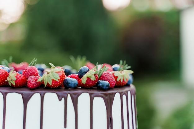 Gâteau de mariage avec des fraises et des myrtilles sur le dessus