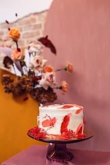 Gâteau de mariage près de l'arche de mariage avec des fleurs à l'intérieur avec des murs de briques.