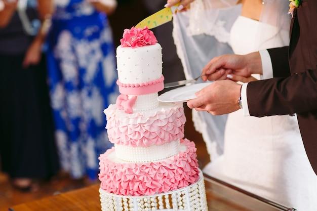Gâteau de mariage rose. la mariée et le marié se tiennent près d'un gâteau de mariage.