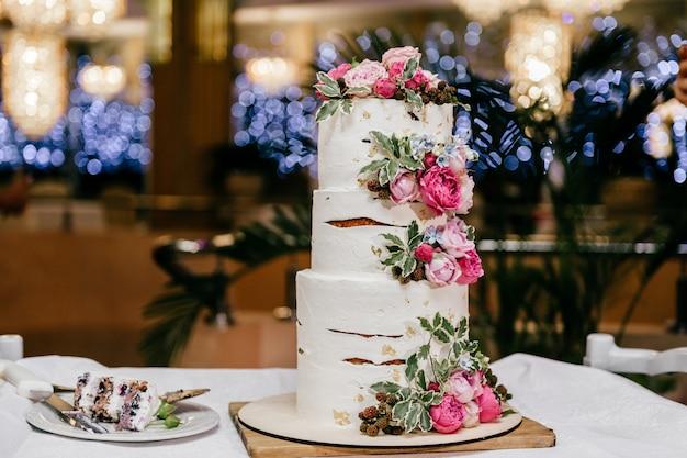 Gâteau de mariage à trois niveaux avec du mastic blanc et des pivoines isolés