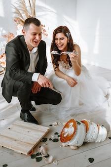 Un gâteau de mariage à trois niveaux qui est tombé de la table. la mariée nourrit le marié les restes d'un gâteau tombé