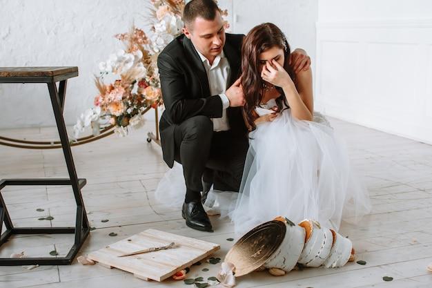 Gâteau de mariage à trois niveaux tombant de la table. émotions de la mariée et du marié lorsque le gâteau tombe