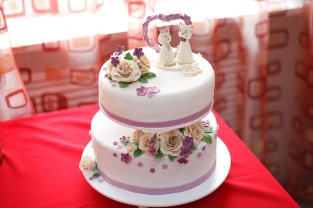 Gâteau de mastic de mariage décoré de fleurs et de figures de chat, gros plan