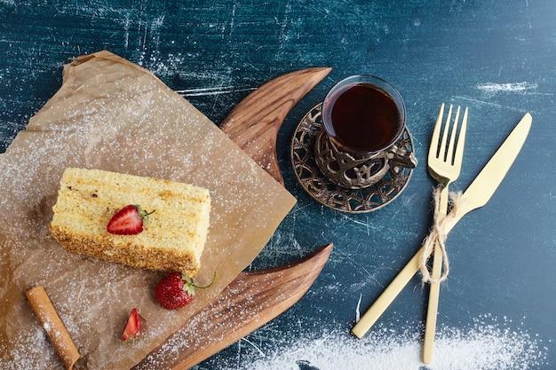 Gâteau medovic avec un verre de thé, vue du dessus.